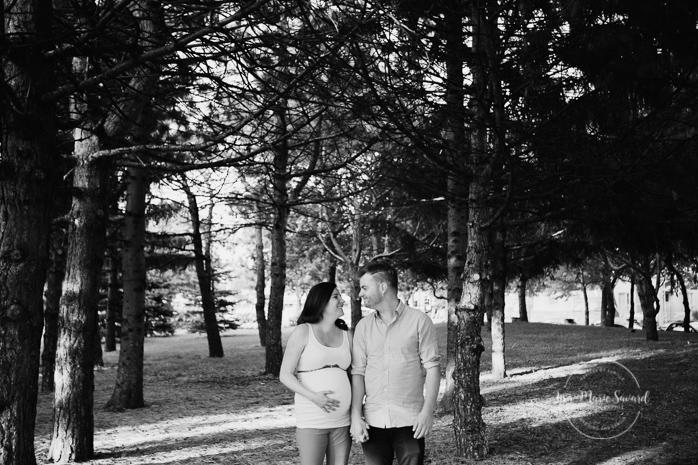 Maternity session at the park couple side by side holding hands in the forest Jarry Park Montreal. Séance maternité lifestyle au Parc Jarry à Montréal |Lisa-Marie Savard Photographie |Montréal, Québec |www.lisamariesavard.com