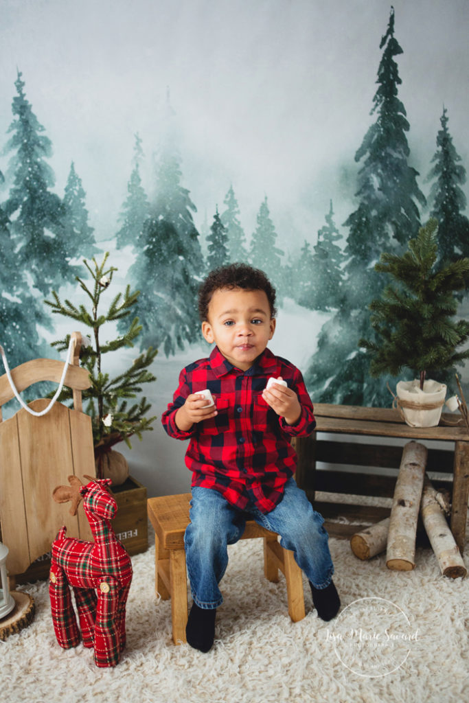 Christmas mini sessions decor idea holiday mini sessions set-up Intuition Backgrounds Vale winter wonderland fake snow faux fur plaid lumberjack deer pine trees balsam fir wood sled fireplace marshmallows. Children boy girl eating marshmallows mini session idea. Minis séances des Fêtes 2017 séance photo en studio pour enfants à Montréal | Lisa-Marie Savard Photographie | Montréal, Québec | www.lisamariesavard.com