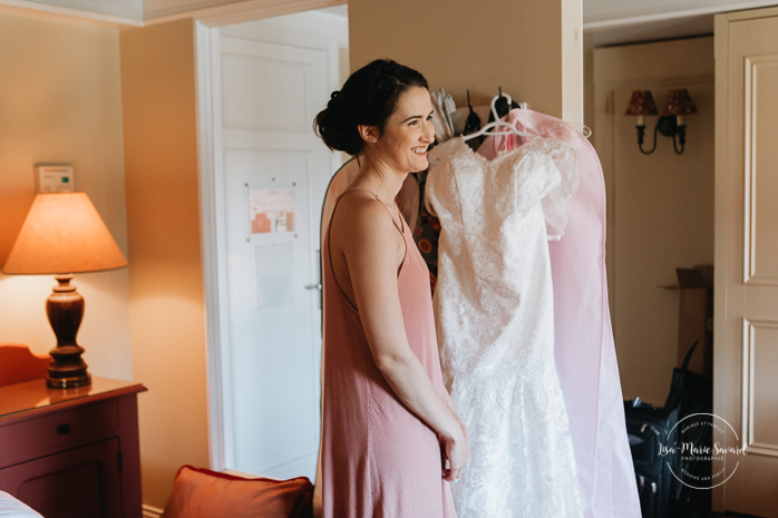 Bride looking at her dress while smiling laughing. Bride getting ready with her bridesmaids in a hotel room. Simple intimate wedding in Quebec City. Outdoor wedding in Quebec City. Quebec City wedding photographer. Mariage au Manoir du Lac Delage. Mariage à Québec. Photographe de mariage à Québec. Mariage Lac Delage | Lisa-Marie Savard Photographie |Montréal, Québec | www.lisamariesavard.com