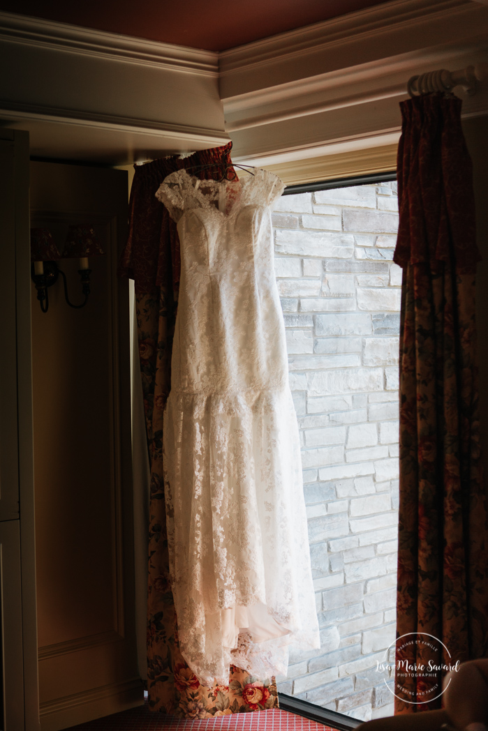 Wedding dress hanging by window. Wedding gown hanging in front of window. Bride getting ready with her bridesmaids in a hotel room. Simple intimate wedding in Quebec City. Outdoor wedding in Quebec City. Quebec City wedding photographer. Mariage au Manoir du Lac Delage. Mariage à Québec. Photographe de mariage à Québec. Mariage Lac Delage | Lisa-Marie Savard Photographie |Montréal, Québec | www.lisamariesavard.com