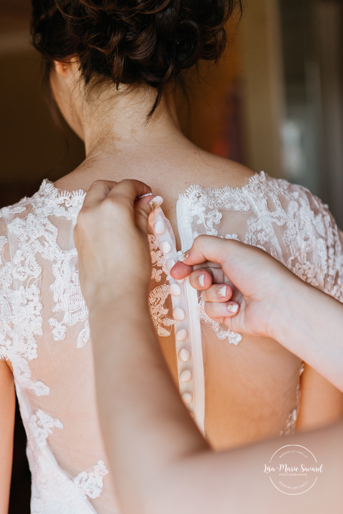 Bridesmaid helping bride putting her dress on. Bridesmaids zipping the bride's dress. Bride getting ready with her bridesmaids in a hotel room. Simple intimate wedding in Quebec City. Outdoor wedding in Quebec City. Quebec City wedding photographer. Mariage au Manoir du Lac Delage. Mariage à Québec. Photographe de mariage à Québec. Mariage Lac Delage | Lisa-Marie Savard Photographie | Montréal, Québec | www.lisamariesavard.com