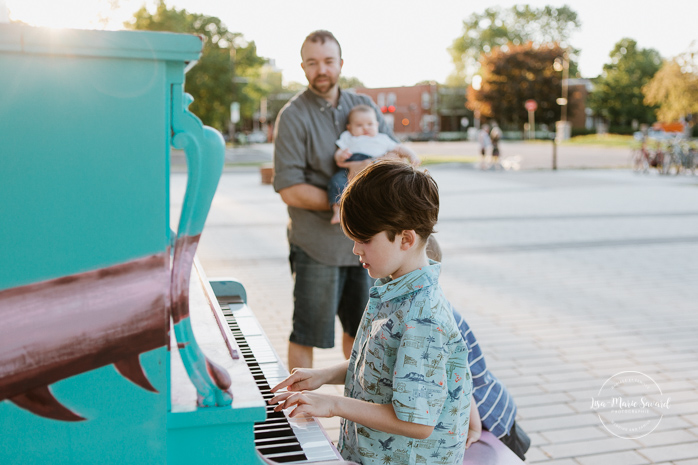 Dad playing piano with sons. Photographe de famille à Montréal. Quai 5160 maison de la culture. Piano public Quai 5160. Montreal family photographer.