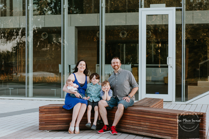 Family sitting on bench in front of a glass building. Outdoor urban family photos. Quai 5160 maison de la culture.