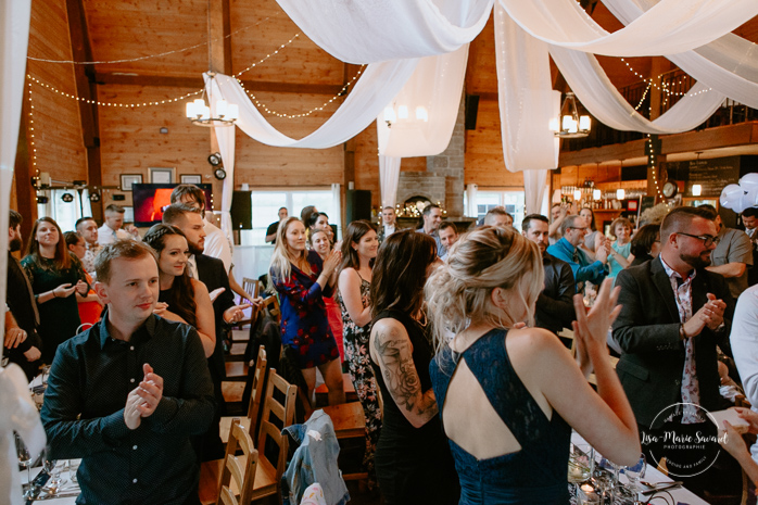 Rustic reception inside old barn. Guest clapping and laughing during reception. Photographe de mariage au Saguenay.