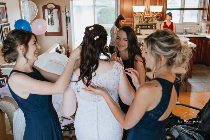 Bridesmaid putting earrings on. Photographe de mariage au Saguenay.