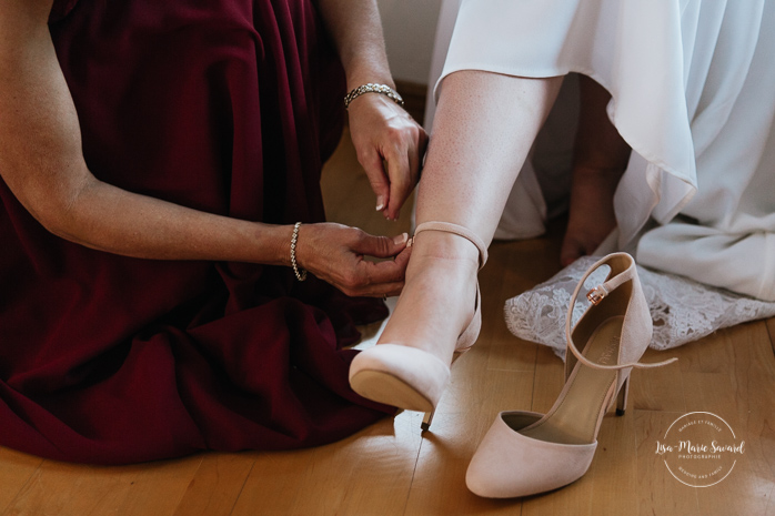 Mother puts bride's shoes on. Photographe de mariage au Saguenay.