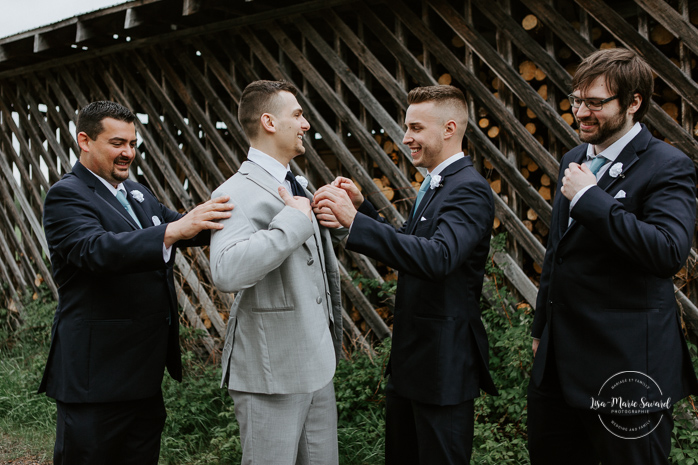 Groom getting ready outside with groomsmen in front of log pile. Photographe de mariage au Saguenay.