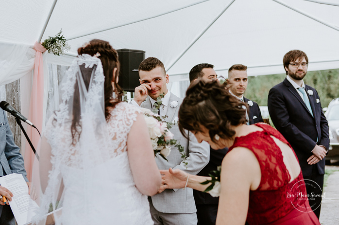 Groom reaction when seeing bride walking down the aisle. Outdoor wedding ceremony in front of old barn. Mariage à l'Orée des Champs au Lac-Saint-Jean. Photographe de mariage au Saguenay.