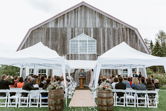 Outdoor wedding ceremony in front of old barn. Mariage à l'Orée des Champs au Lac-Saint-Jean. Photographe de mariage au Saguenay.