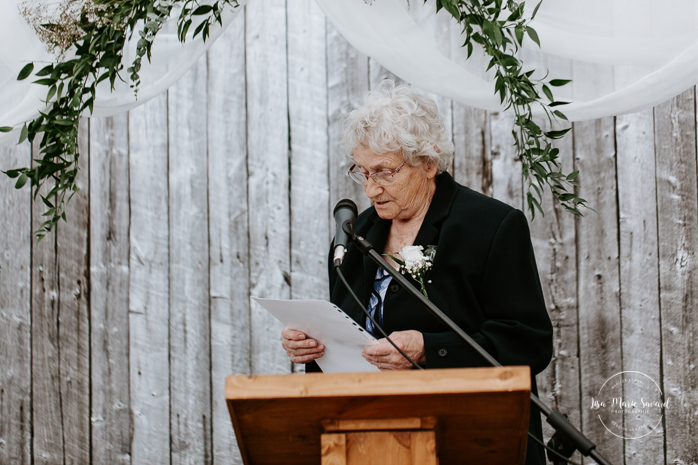 Grandmother reading letter to bride and groom during ceremony. Outdoor wedding ceremony in front of old barn. Mariage à l'Orée des Champs au Lac-Saint-Jean. Photographe de mariage au Saguenay.