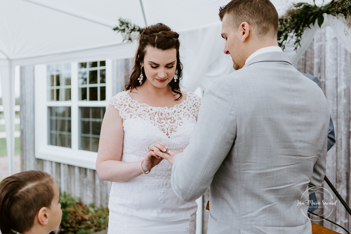 Bride and groom exchanging rings. Outdoor wedding ceremony in front of old barn. Mariage à l'Orée des Champs au Lac-Saint-Jean. Photographe de mariage au Saguenay.