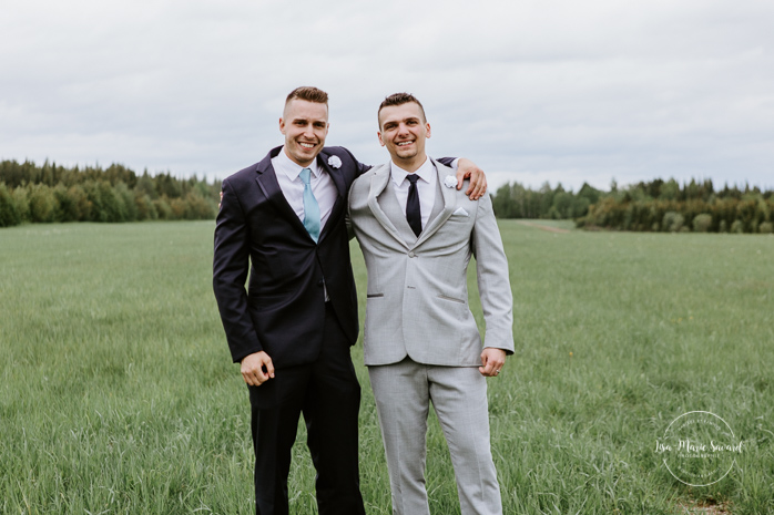 Wedding party photos with three groomsmen. Rustic wedding in a field. Photographe de mariage au Saguenay.