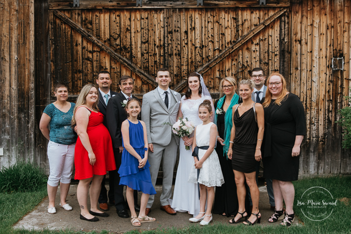Wedding family photos in front of old wood barn. Rustic wedding in a field. Photographe de mariage au Saguenay.