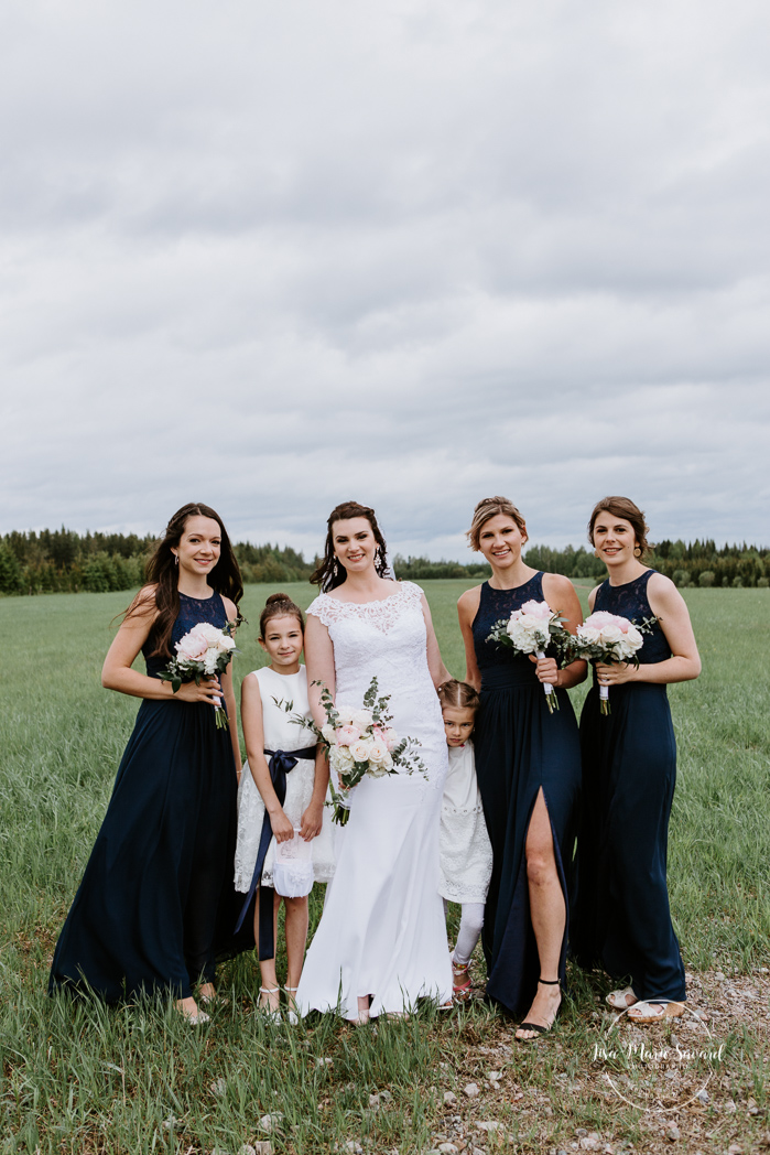 Wedding party bridal party photos with three bridesmaids. Rustic wedding in a field. Photographe de mariage au Saguenay.