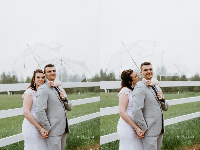 Rainy wedding pictures with clear umbrellas. Rustic wedding in a field. Mariage à l'Orée des Champs au Lac-Saint-Jean. Photographe de mariage au Saguenay.