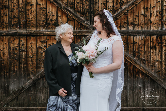 Wedding family photos with grandmother in front of old wood barn. Rustic wedding in a field. Photographe de mariage au Saguenay.