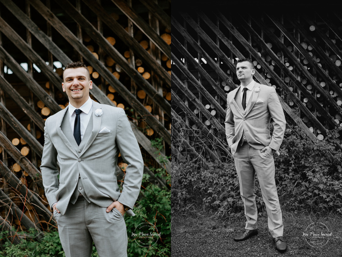 Groom portrait standing up in front of log pile. Photographe de mariage au Saguenay.