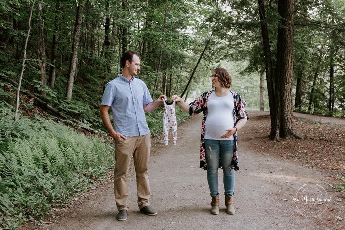 Forest maternity photos. Onesie maternity photos. Parents holding onesie pregnancy announcement. Photographe de grossesse sur la Rive-Nord. Parc régional de la Rivière du Nord. Montreal maternity photographer