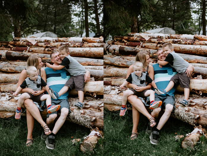 Lifestyle family session at home. Family sitting on log pile. Séance familiale à domicile à Saguenay. Séance photo à Laterrière. Saguenay family photographer.