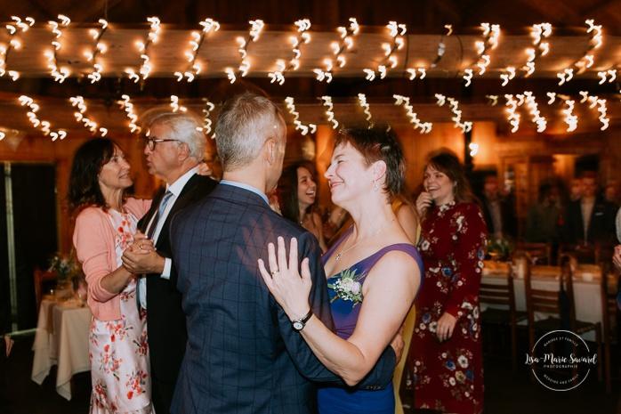 Wedding guests dancing and partying. Wedding reception inside wooden cabin sugar shack. Réception de mariage à la Table du Roy cabane à sucre Auberge Le Baluchon. Photographe de mariage à Trois-Rivières