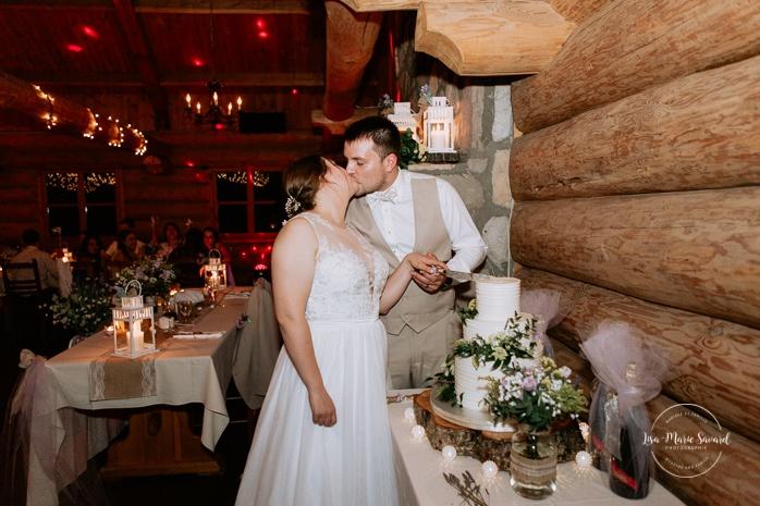 Bride and groom cutting cake. Wedding reception inside wooden cabin sugar shack. Réception de mariage à la Table du Roy cabane à sucre Auberge Le Baluchon. Photographe de mariage à Trois-Rivières