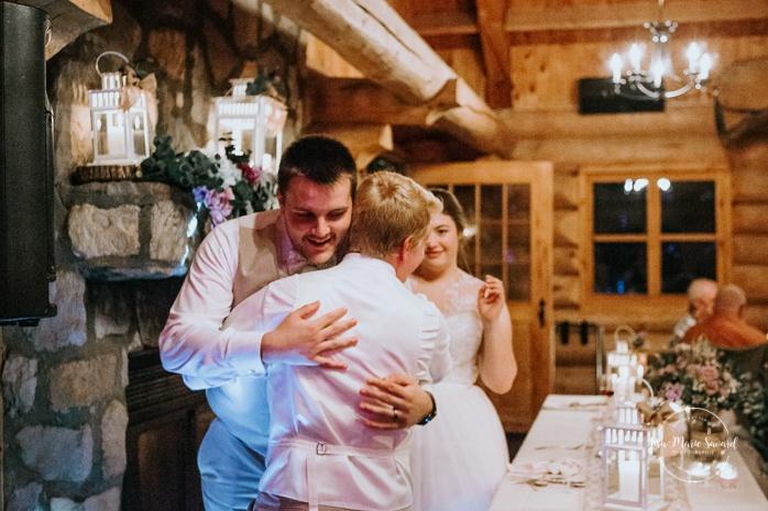 Best man doing speech during reception. Wedding reception inside wooden cabin sugar shack. Réception de mariage à la Table du Roy cabane à sucre Auberge Le Baluchon. Photographe de mariage à Trois-Rivières