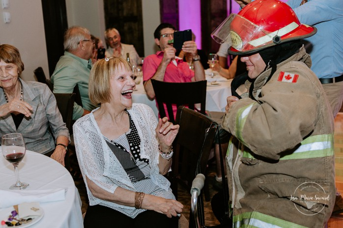Firefighter groom doing a funny striptease to his wife. Mariage à Sainte-Agathe-des-Monts. Mariage an golf de Val-Morin. Photographe de mariage dans les Laurentides. Laurentians wedding photographer.