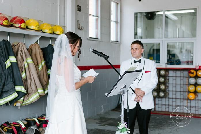 Bride reading vows to groom during ceremony. Wedding inside a real fire station. Mariage dans une caserne de pompier. Mariage à Sainte-Agathe-des-Monts. Photographe de mariage dans les Laurentides. Laurentians wedding photographer.