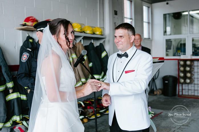 Bride and groom exchanging rings. Wedding inside a real fire station. Mariage dans une caserne de pompier. Mariage à Sainte-Agathe-des-Monts. Photographe de mariage dans les Laurentides. Laurentians wedding photographer.