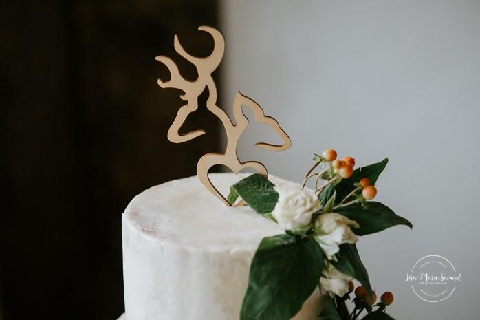 Three tier white wedding cake with flowers and greenery. Deer cake topper. Mariage à Sainte-Agathe-des-Monts. Mariage an golf de Val-Morin. Photographe de mariage dans les Laurentides. Laurentians wedding photographer.