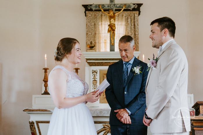 Bride reading vows to groom. Small chapel wedding. Mariage à l'Auberge Le Baluchon éco-villégiature en Mauricie. Chapelle Auberge Le Baluchon à Saint-Paulin. Photographe de mariage à Trois-Rivières