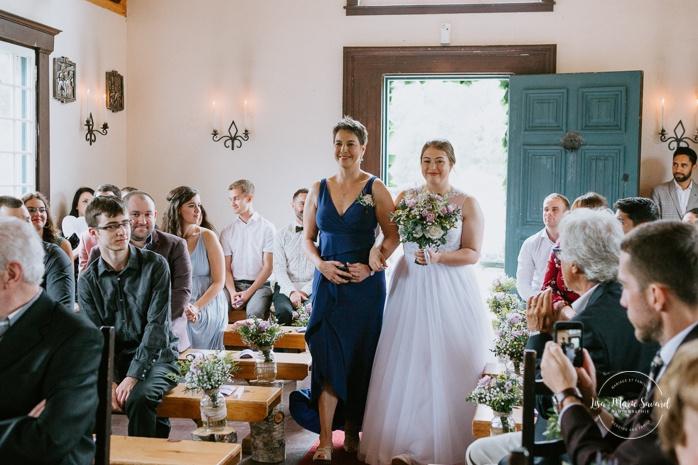 Bride and mom walking down the aisle Small chapel wedding. Mariage à l'Auberge Le Baluchon éco-villégiature en Mauricie. Chapelle Auberge Le Baluchon à Saint-Paulin. Photographe de mariage à Trois-Rivières