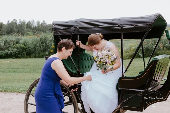 Bride arriving to wedding ceremony by horse drawn carriage. Small chapel wedding. Mariage à l'Auberge Le Baluchon éco-villégiature en Mauricie. Chapelle Auberge Le Baluchon à Saint-Paulin. Photographe de mariage à Trois-Rivières
