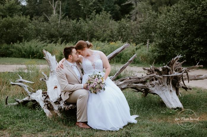 Bride and groom sitting on large drift wood. Photos de mariage rustique à la campagne. Photographe de mariage à Trois-Rivières