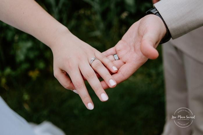 Bride and groom holding hands to show off rings. Photos de mariage rustique à la campagne. Photographe de mariage à Trois-Rivières