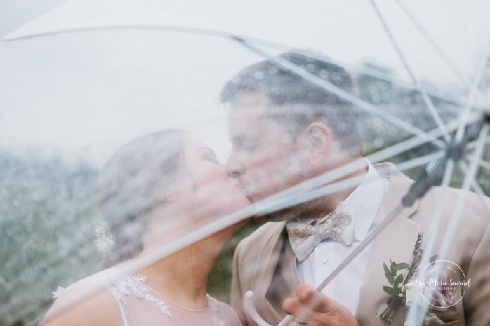Rainy wedding photos under clear umbrellas. Photos de mariage rustique à la campagne. Photographe de mariage à Trois-Rivières