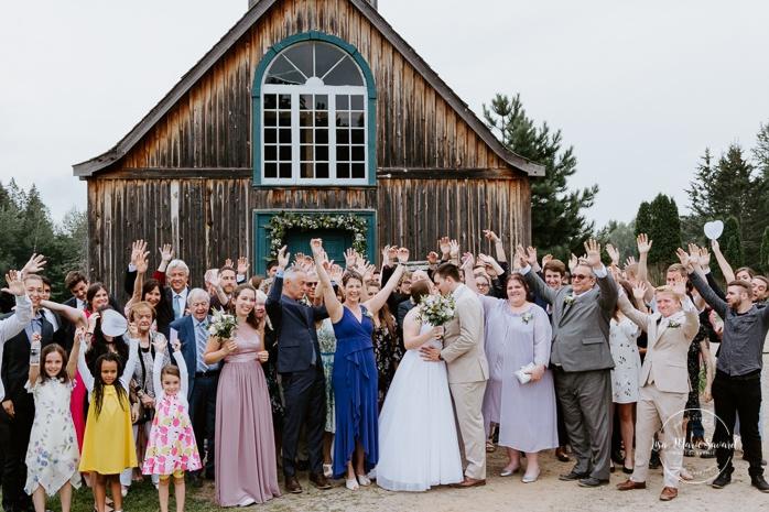 Group photo with 80 guests in front of chapel. Small chapel wedding. Mariage à l'Auberge Le Baluchon éco-villégiature en Mauricie. Chapelle Auberge Le Baluchon à Saint-Paulin. Photographe de mariage à Trois-Rivières