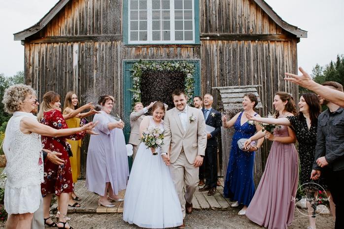 Guests throwing lavender at newlyweds outside of chapel. Small chapel wedding. Mariage à l'Auberge Le Baluchon éco-villégiature en Mauricie. Chapelle Auberge Le Baluchon à Saint-Paulin. Photographe de mariage à Trois-Rivières