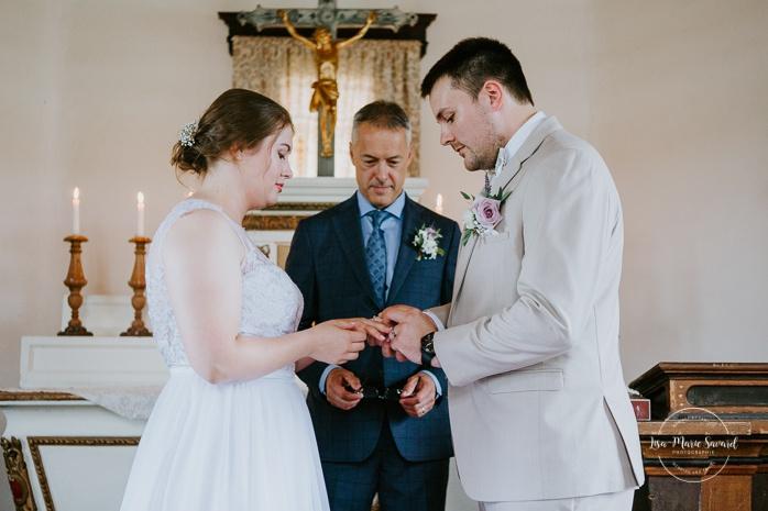 Bride and groom exchanging rings. Small chapel wedding. Mariage à l'Auberge Le Baluchon éco-villégiature en Mauricie. Chapelle Auberge Le Baluchon à Saint-Paulin. Photographe de mariage à Trois-Rivières
