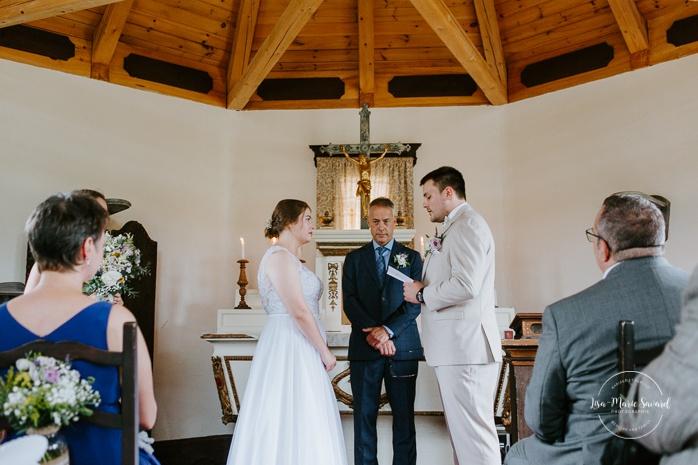 Groom reading vows to bride. Small chapel wedding. Mariage à l'Auberge Le Baluchon éco-villégiature en Mauricie. Chapelle Auberge Le Baluchon à Saint-Paulin. Photographe de mariage à Trois-Rivières