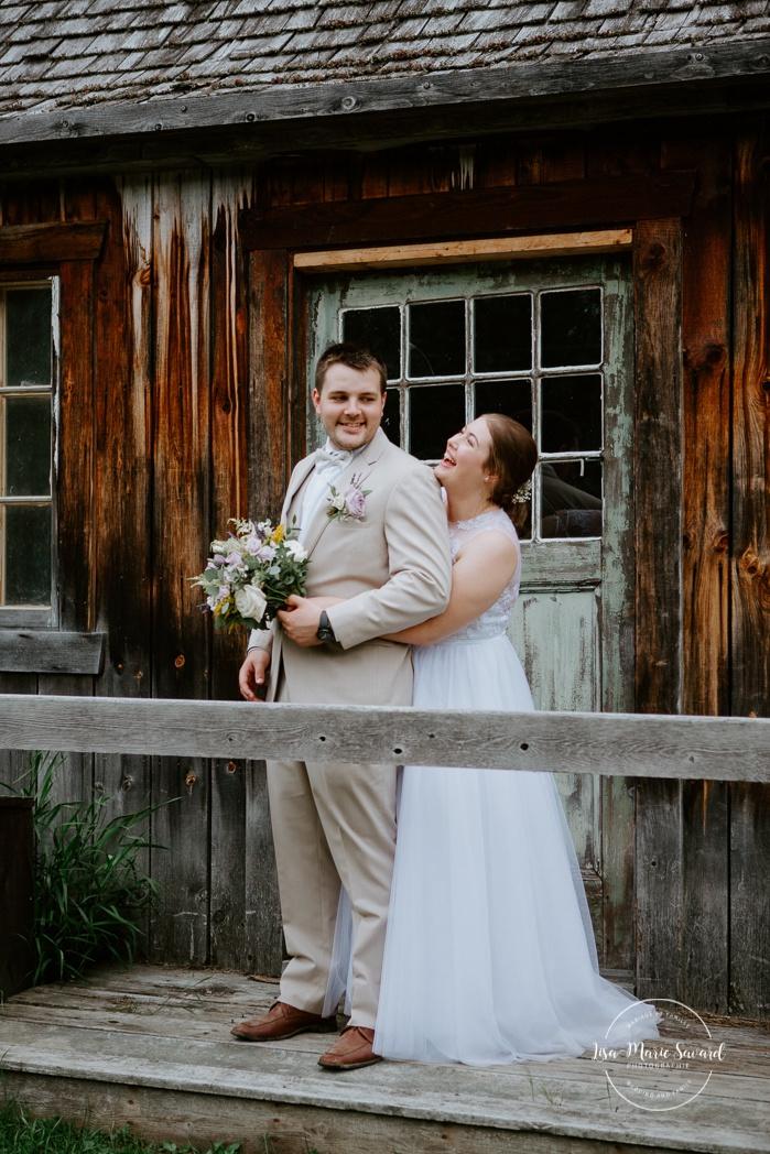 Bride hugging groom from behind. Photos de mariage rustique à la campagne. Photographe de mariage à Trois-Rivières