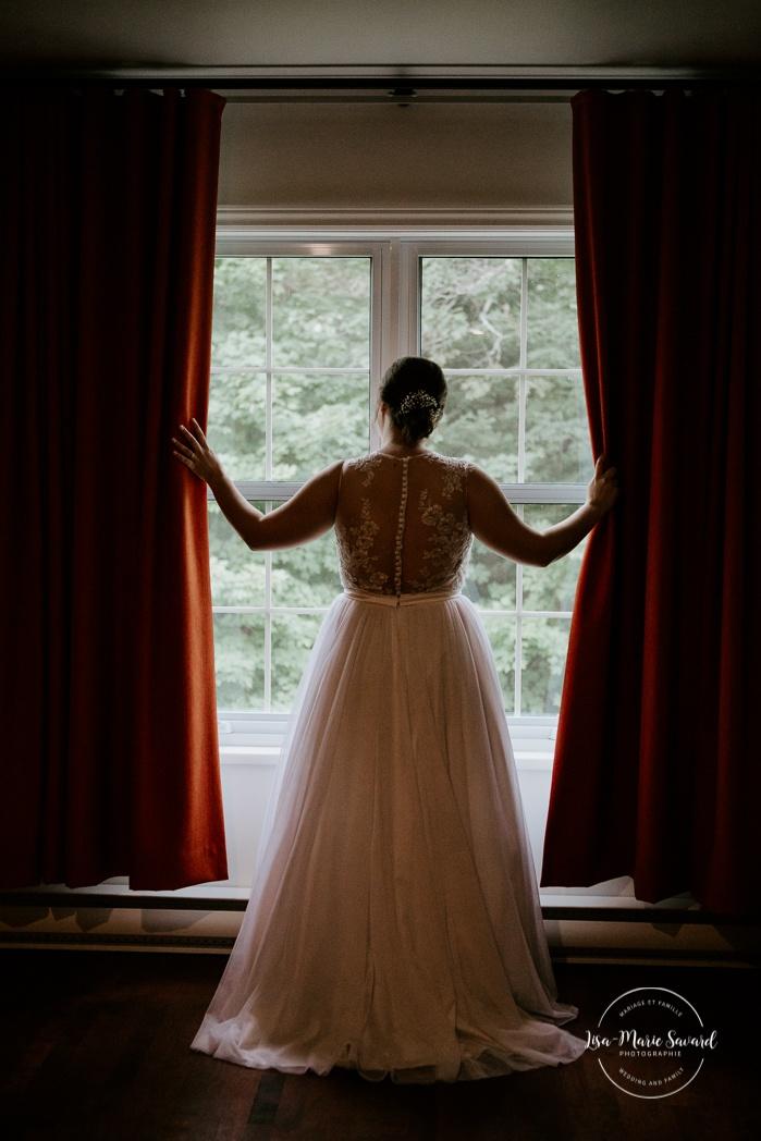Bride looking out of hotel room window. Auberge de l'Archipel à Saint-Paulin. Préparations des mariés à l'hôtel. Photographe de mariage à Trois-Rivières