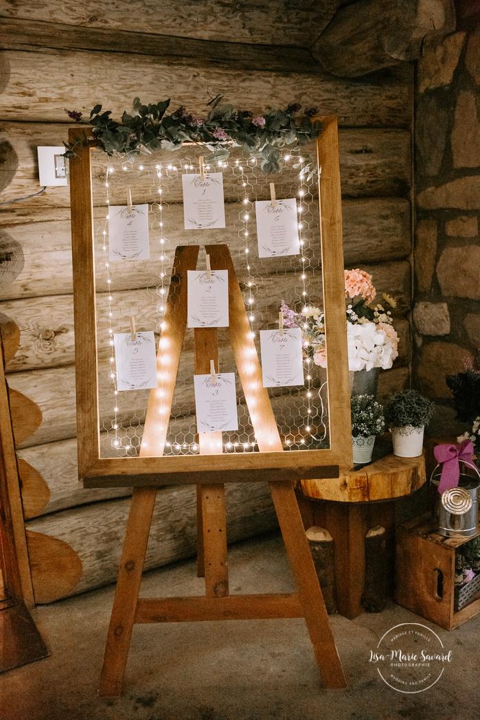 Rustic wedding reception decor. Seating chart with old wooden frame. Wedding reception inside wooden cabin sugar shack. Réception de mariage à la Table du Roy cabane à sucre Auberge Le Baluchon. Photographe de mariage à Trois-Rivières