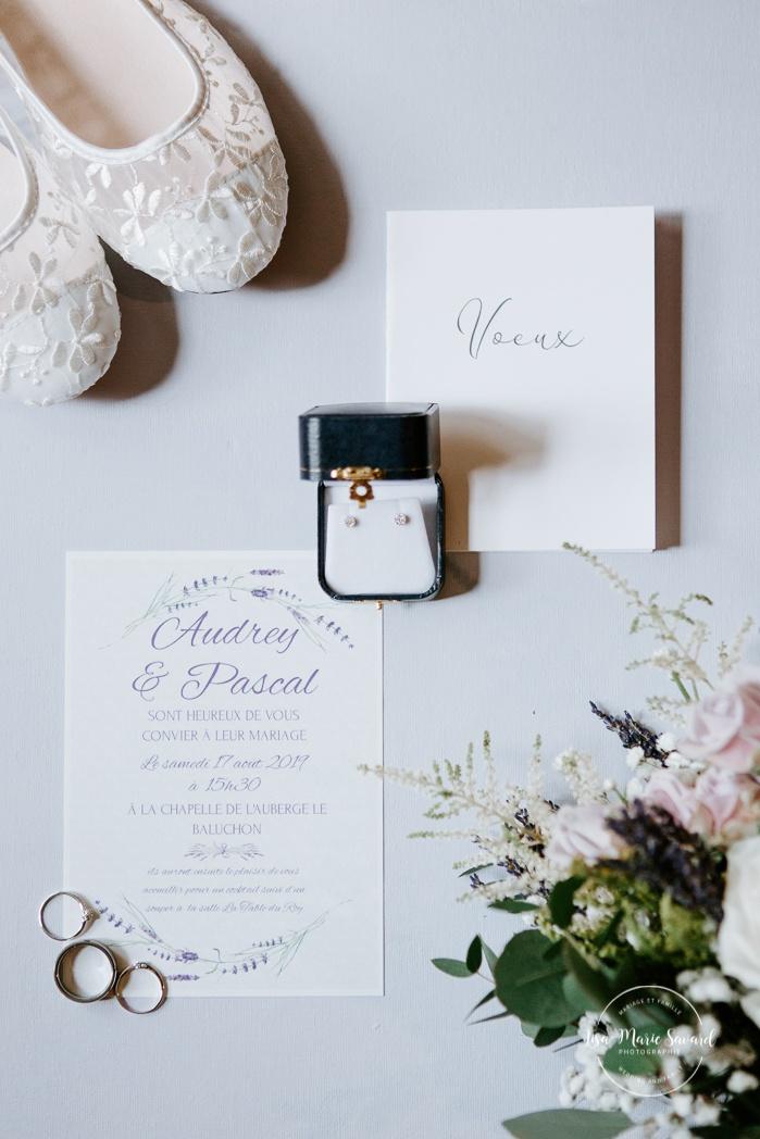Lay flat wedding detail with shoes, invitation, vow book, jewellery, ring and bouquet. Auberge de l'Archipel à Saint-Paulin. Préparations des mariés à l'hôtel.