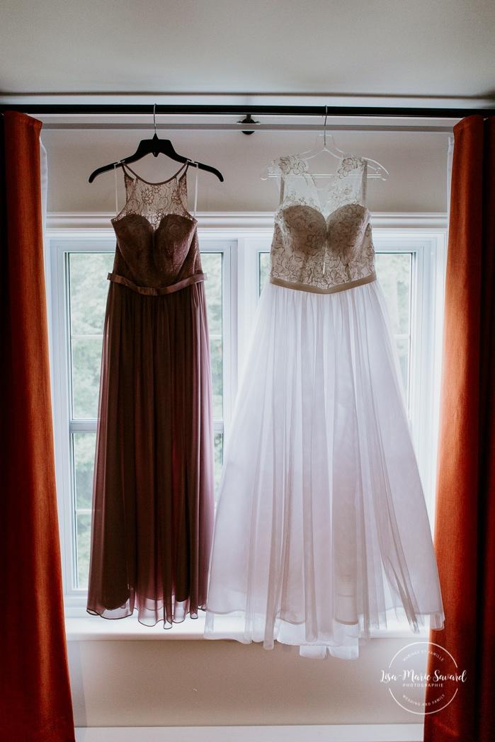 Bride gown and bridesmaid dress hanging in front of window. Auberge de l'Archipel à Saint-Paulin. Préparations des mariés à l'hôtel.