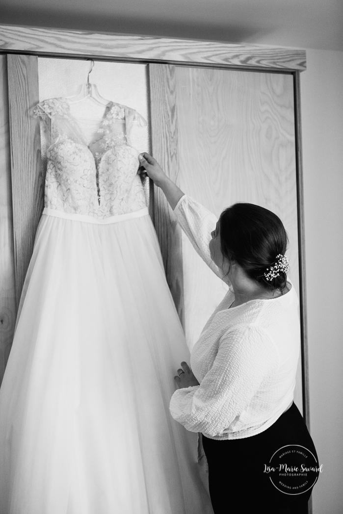 Bride looking at dress hanging from wardrobe in hotel room. Auberge de l'Archipel à Saint-Paulin. Préparations des mariés à l'hôtel. Photographe de mariage à Trois-Rivières