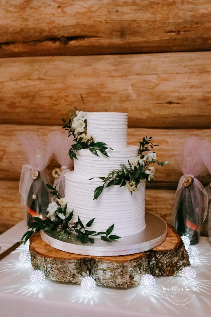 Rustic wedding reception decor. Simple three tier wedding cake with wildflowers and greenery. Wedding reception inside wooden cabin sugar shack. Réception de mariage à la Table du Roy cabane à sucre Auberge Le Baluchon. Photographe de mariage à Trois-Rivières