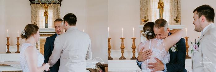 Bride's father hugging newlyweds after ceremony. Small chapel wedding. Mariage à l'Auberge Le Baluchon éco-villégiature en Mauricie. Chapelle Auberge Le Baluchon à Saint-Paulin. Photographe de mariage à Trois-Rivières