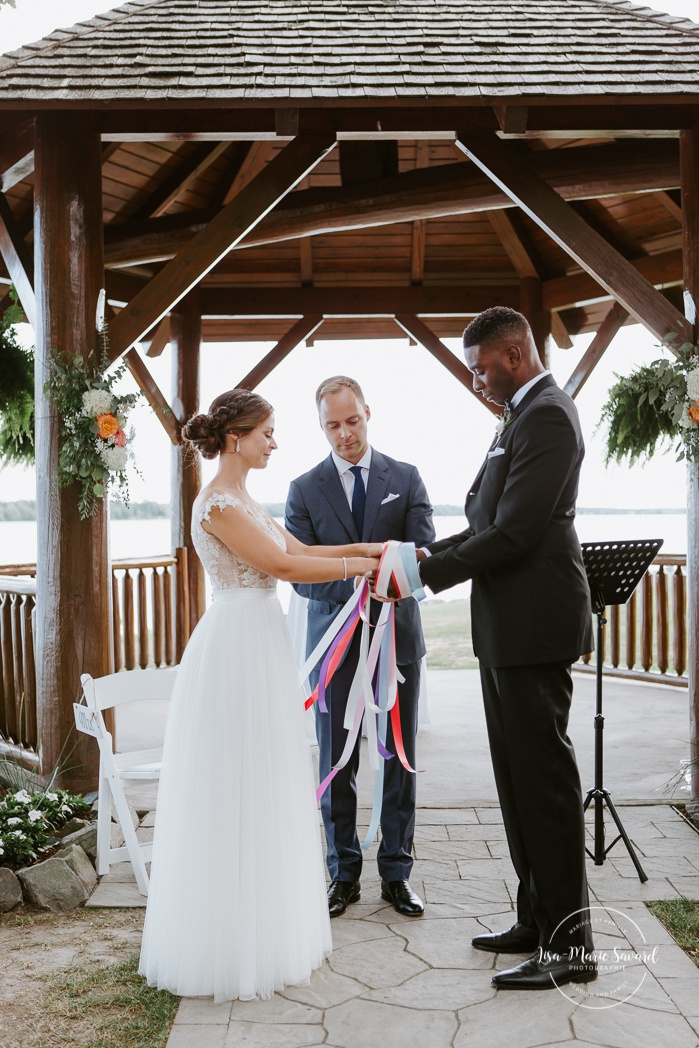Handfasting ceremony with ribbons. Cérémonie de mariage extérieure au Château Montebello. Fairmont Le Château Montebello outdoor wedding. Ottawa photographer.