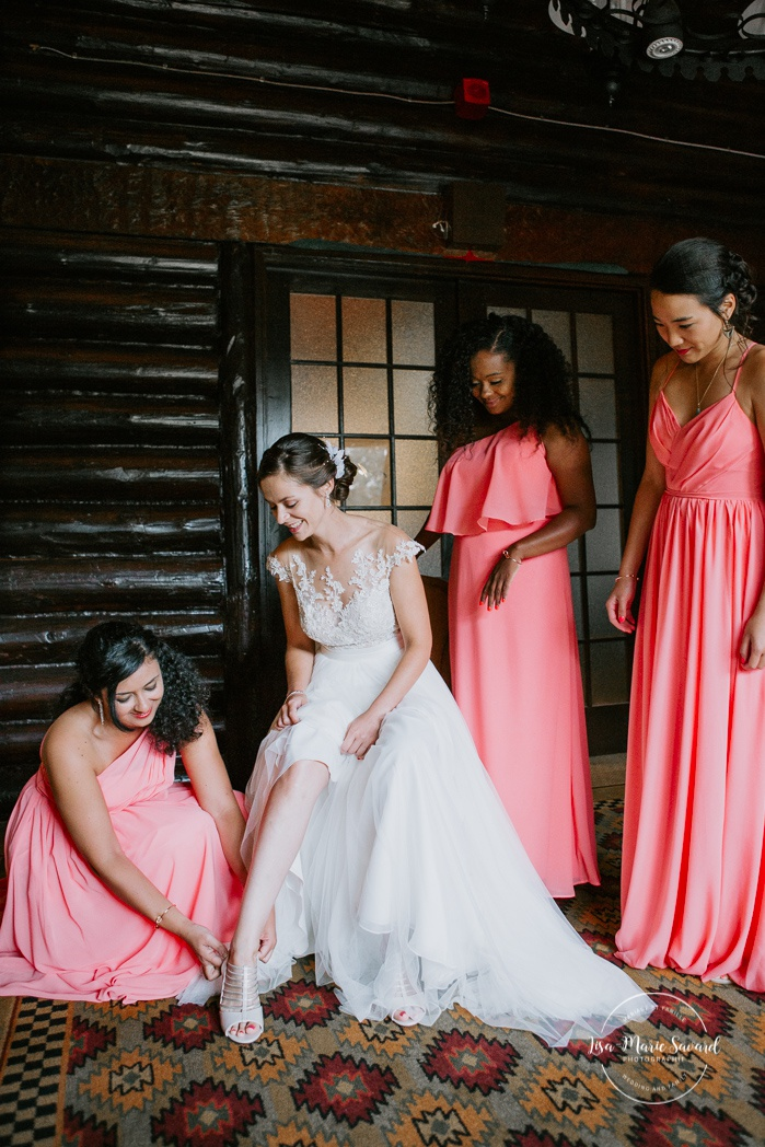Bridesmaid helping bride put on shoes. Mariage en Outaouais. Fairmont Le Château Montebello wedding. Ottawa photographer.